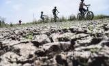 Anak-anak bermain di area lahan pertanian yang mengalami kekeringan di Gedebage, Kota Bandung, Rabu (26/6).