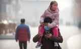 Anak perempuan mengenakan masker masker di atas gendongan seorang pria sambil menyusuri jalanan di Beijing, China, Selasa (28/1). Kematian akibat corona pertama terjadi di luar Wuhan, yakni di Beijing. Selandia Baru akan sewa pesawat menuju Wuhan untuk memulangkan warganya dari Wuhan. Ilustrasi.