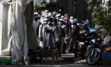Anggota Jamaah Tabligh menunggu bus yang akan membawa mereka ke fasilitas karantina di Nizamuddin, New Delhi, India, Selasa (31/3). Jamaah Tabligh tetap menggelar pertemuan di tengah kekhawatiran meluasnya penyebaran virus corona.