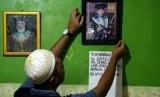 Anggota keluarga memperbaiki posisi foto Sudirdjo, seorang petugas Kelompok Penyelenggara Pemungutan Suara (KPPS) Pemilu serentak 2019 yang meninggal dunia usai mendapatkan perawatan di rumah sakit di Bekasi, Jawa Barat, Selasa (23/4/2019).