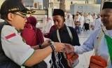Anggota Tim Pertolongan Pertama Pada Jamaah Haji (P3JH) memberikan masker kepada jamaah haji asal Lombok di Masjid Al Haram, Jumat (19/7).