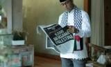 Anies Baswedan mengenakan syal berbendara Palestina sambil membaca koran Republika, Jumat (8/12).