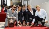 Backstreet Boys (dari kiri) A. J. McLean, Howie Dorough, Kevin Richardson, Nick Carter dan Brian Littrell menyentuh bintang mereka di Walk of Fame, Los Angeles, Senin (22/4/2013)