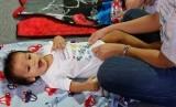 Bayi hendak diganti popoknya oleh ibunya.