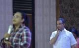 Calon gubernur DKI Jakarta nomor urut tiga, Anies Baswedan (kanan) menyimak paparan timses Ahok-Djarot ketika menghadiri Festival Budaya Perempuan 1001 Cerita Perempuan Kali Ciliwung di GOR Otista, Jakarta, Kamis (8/12).