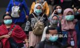 Calon pengguna transportasi umum mengenakan masker saat melintasi kawasan Terowongan Kendal, Jakarta, Kamis (12/3/2020).