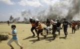 Dalam foto dokumentasi tanggal 14 Mei 2018 ini, petugas medis Palestina dan pengunjuk rasa mengevakuasi seorang pemuda yang terluka selama berlangsungnya protes di perbatasan Jalur Gaza dengan Israel, di sebelah timur Khan Younis, Jalur Gaza. Negara-negara Arab dengan tegas mengutuk pembunuhan lebih dari 50 warga Palestina pada Senin, 14 Mei 2018 dalam protes Gaza.