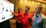 Direktur Sales Telkomsel, Mas'ud Khamid (tengah) dan Commisioner BRTI I Ketut Prihadi (kanan), menunjukkan proses registrasi pelanggan prabayar.
