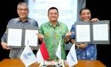 Direktur Utama PGN Gigih Prakoso (kiri) dan Direktur Utama Pelindo III Doso Agung (kanan) disaksikan Deputi Bidang Usaha Energi, Logistik, Kawasan dan Pariwisata Kementerian BUMN, Edwin Hidayat Abdullah (tengah) menunjukkan nota kerjasama seusai penandatanganan di Jakarta, Rabu (26/6/2019).
