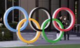 Dua orang berdiri di belakang logo Olimpiade di Tokyo, Jepang. Virus corona telah mengancam kemungkinan terselenggaranya Olimpiade 2020 di Tokyo.