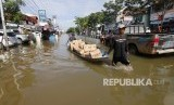 Dua pria menarik perahu yang disewakan untuk mengangkut puluhan barang milik pemilik toko yang dievakuasi dari kawasan Jalan A Yani yang terendam banjir di Samarinda, Kalimantan Timur, Rabu (12/6/2019).