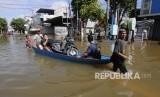 Dua pria menarik perahu yang disewakan untuk mengangkut warga dan motor dari kawasan Jalan A Yani yang terendam banjir di Samarinda, Kalimantan Timur, Rabu (12/6/2019).