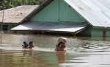 Dua warga menerobos banjir yang terjadi di Desa Tonduno, Konawe Selatan, Sulawesi Tenggara, Senin (17/6/2019).