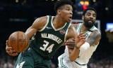 Forward Milwaukee Bucks Giannis Antetokounmpo (34) membawa bola melewati guard Boston Celtics Kyrie Irving pada gim ketiga babak kedua play-off NBA, Sabtu (4/5) WIB.