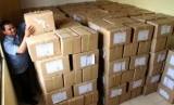 Ilustrasi petugas logistik menata tumpukan kotak berisikan kertas surat suara.