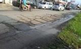 Jalan raya Babelan, Kecamatan Babelan, Kabupaten Bekasi, berlubang-lubang dan membuat pengendara terpaksa memperlambat laju kendaraannya.