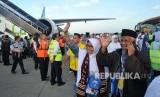 Jamaah calon haji melambaikan tangan kepada keluarga mereka, menjelang keberangkatan kloter pertama embarkasi Padang, di Bandara Internasional Minangkabau (BIM), Padangpariaman, Sumatera Barat, Selasa (17/7).