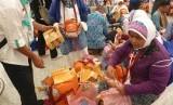 Jamaah haji embarkasi SOC 48 asal Tegal, Saronah Sakib Wajad (59 tahun) dengan dibantu petugas haji membuang kemasan mainan hasil buruannya di Makkah, di Paviliun Haji Bandara Amir Muhammad Bin Abdul Aziz, Madinah, Kamis (21/9).