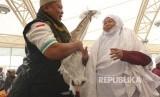 Jamaah haji embarkasi SOC 48 asal Tegal, Widjah Daklan (59 tahun) terpaksa mengenakan tiga rangkap mukena dan sajadah karena tasnya tak muat lagi.
