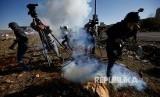 Jurnalis berlarian menghindari gas air mata yang ditembakkan tentara Israel di Kota Ramallah, Tepi Barat, Palestina.