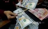 Karyawan menghitung mata uang Dolar AS di penukaran valuta asing Ayu Masagung, Jakarta, Ahad (9/7).