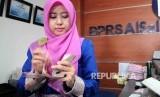 Karyawati menghitung uang di Bank Pembiayaan Rakyat Syariah (BPRS) Al Salaam, Jakarta, Selasa (6/12).