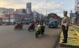 Kasatlantas Polrestro Depok, Kompol Sutomo sedang mengatur lalulintas di Jalan Margonda, Depok.