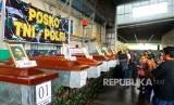 Keluarga korban berada di dekat peti berisi jenazah korban penembakan kelompok kriminal bersenjata (KKB) saat diserahterimakan di hanggar Avco Bandara Moses Kilangin Timika, Mimika, Papua, Jumat (7/12/2018).