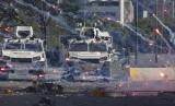 Kembang api dilempar demonstran antipemerintah Venezuela mendarat di dekat kendaraan lapis baja Garda Nasional Bolivarian di Caracas, Venezuela, Selasa (30/4).