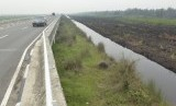 Kendaraan melintas di samping sekat kanal lahan gambut di Jembatan Tumbang Nusa, Kalteng, Kamis (29/10).