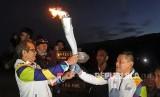 Kepala Balai Besar KSDA Jawa Timur Nandang Prihadi (kiri), menerima obor Asian Games 2018 dari mantan petinju Pino Bahari di puncak Gunung Ijen, Banyuwangi, Jawa Timur, Ahad (22/7).