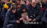Kerabat membawa foto korban saat peti jenazah korban pesawar Ukraine International Airlines nomor penerbangan 752 dibawa dalam upacara militer di Boryspil International Airport, pinggiran Kiev, Ukraine Ahad (19/1) waktu setempat.