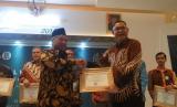 Ketua Badan Pelaksana Badan Wakaf Indonesia, Muhammad Nuh (kiri) Direktur Utama BNI Syariah, Abdullah Firman Wibowo (kanan) saat penyerahan penghargaan sebagai bank syariah yang aktif dalam mendukung wakaf produktif di Indonesia melalui aplikasi dan website Wakaf Hasanah.