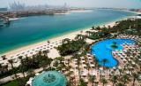 Kolam renang dan pantai Atlantis Hotel terlihat dengan cakrawala Dubai Marina yang terlihat di kejauhan di Dubai, Uni Emirat Arab, Selasa, 14 Juli 2020. Dubai telah dibuka kembali untuk para wisatawan, termasuk di Atlantis di Dubai yang dibuat oleh manusia buatan Dubai. Kepulauan Palm Jumeirah, meskipun pekerja di sana mengharapkan pertumbuhan yang lambat sepanjang tahun di tengah pandemi coronavirus yang sedang berlangsung.