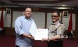 Komisioner Ombudsman Adrianus Meliala (kiri) menyerahkan surat laporan hasil pemerksaan kepada Itwasum Wilayah (Irwil) IV Mabes Polri Brigjen Pol Endang Surya Darma (kanan) saat penyerahan surat pemeriksaan Laporan Akhir Hasil Pemeriksaan (LAHP) di Kantor Ombudsman, Jakarta, Selasa (13/2).