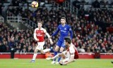 Leurent Koscielny menjatuhkan badan saat mencetak gol kedua Arsenal ke gawang Chelsea.