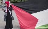 Seorang perempuan memegang bendera Palestina saat aksi protes, ilustasi