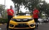 Marketing and After Sales Director PT Honda Prospest Motor Jonfis Fandy (kiri) bersama Businesss and Product Planning Director PT Honda Prospect Motor Takayuki Uotani (kanan) berfoto bersama di mobil All New Honda Brio seusai serah terima mobil kepada konsumen di Jakarta, Sabtu (13/10).