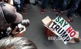 Massa aksi damai darurat Yerusalem membakar kardus dengan kertas bertuliskan Say No To Trump sebagai ganti ban yang sebelumnya dipadamkan oleh kepolisian di depan gedung Kedutaan Besar Amerika Serikat, Jumat (8/12).
