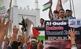 Massa gabungan Ormas Islam Aceh mengusung spanduk, poster dan bendera saat menggelar aksi solidaritas terhadap Palestina di kawasan Masjid Raya Baiturrahman, Banda Aceh, Jumat (8/12).