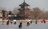 Masyarakat Cina sedang menikmati hiburan bermain seluncur es di Beijing, Cina. Cina dikenal sebagai negara dengan penduduk yang pandai berhemat.