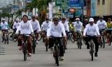 Menko Maritim Luhut B Panjaitan (kedua dari kiri) didampingi Gubernur Maluku Said Assagaff (kiri) bersepeda mengelilingi sejumlah ruas jalan di Kota Ambon usai membuka lomba balap sepeda internasional Tour de Moluccas 2017 di Ambon, Maluku, Ahad (17/8).