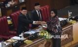 Menteri Keuangan Sri Mulyani Indrawati (kanan) memberikan draft tanggapan pemerintah kepada Ketua Rapat Paripurna Fadli Zon (kiri) didampingi Wakil Ketua DPR Agus Hermanto (tengah) pada Rapat Paripurna DPR di Kompleks Parlemen, Senayan, Jakarta, Selasa (11/6/2019).