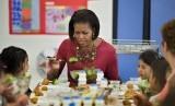 Michelle Obama mendampingi anak-anak makan di sekolahnya saat menggagas program makan sehat.