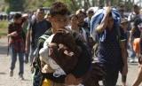 Migran dari Amerika Tengah, bagian dari karavan yang berharap mencapai perbatasan AS, bergerak di jalan di Tapachula, Negara Bagian Chiapas, Meksiko. Penutupan sistem suaka dilakukan untuk pertama kalinya dalam beberapa dekade akibat pandemi Covid-19. Ilustrasi.