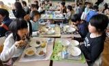 Murid kelas tiga SD di Distrik Edogawa, Tokyo, sedang menikmati makan siang di sekolahnya.