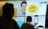 Nasabah melintasi banner iklan penawaran kredit tanpa agunan (KTA) yang ditawarkan di salah satu kantor cabang Bank Mandiri, Jakarta.