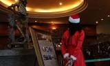 Pekerja mengenakan pakaian atribut natal pada salah satu hotel di Jakarta, Senin (15/12)
