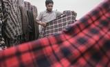 Pedagang bahan tekstil menata kain dagangannya di Sentra Tekstil, Kawasan Cipadu, Tangerang Selatan, Banten, Rabu (25/7). Pemerintah telah menyiapkan peta jalan Making Indonesia 4.0 menyambut revolusi industri.
