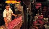 Pedagang mengupas bawang merah sebelum dijual di Pasar Induk Kramat Jati, Jakarta, Ahad (29/1). (Republika/Edwin Dwi Putranto)